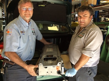 """Jim's Automotive - At Jim's Automotive the phrase, """"We Speak Hybrid"""" is prevalent around the shop. Jim and Henry removing a Prius Hybrid battery."""